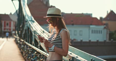 szukanie : Woman using smartphone in the European city. Slow Motion, 4K. Hipster girl browsing Internet on a phone, texting and communicating, standing outdoors on the bridge. Travel.