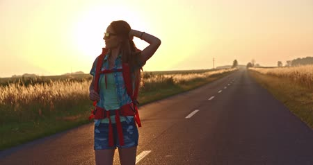 путешествие : Traveler woman walking on a sunny road. Young happy backpacker woman starting a journey on a sunlit country road. Slow motion, 120fps. 4K, DCi. Poland, Lower Silesia