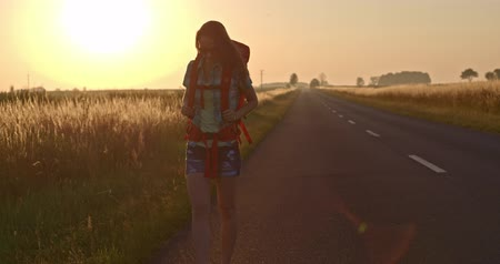 hátizsákkal : Traveler woman hitchhiking on a sunny road and walking. Young happy backpacker woman looking for a ride to start a journey on a sunlit country road. Slow motion, 120fps. 4K, DCi. Poland, Lower Silesia Stock mozgókép