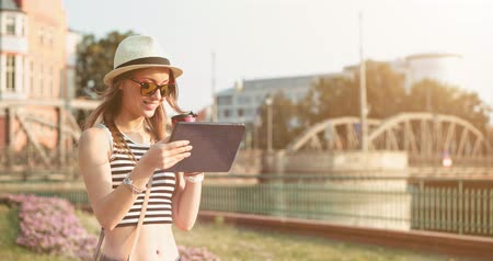 okulary przeciwsłoneczne : Woman using digital tablet and drinking coffee in the European city. Slow Motion, 4K. Hipster girl browsing Internet, searching for maps and information, communicating outdoors. Travel. Lens flare. Wideo
