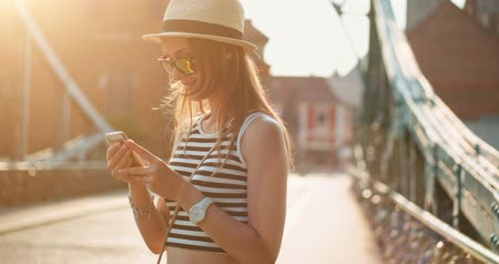 hipster : Woman using smartphone in the European city. Slow Motion, 4K. Hipster girl browsing Internet on a phone, texting and communicating outdoors. Travel. Lens flare. Stock Footage