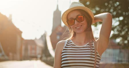 tarz : Beautiful Young Woman smiling in the European city, cinematic portrait. Slow Motion, 4K. Happy Hipster girl enjoying the sun and the life. Travel in style. Lens flare. Stok Video
