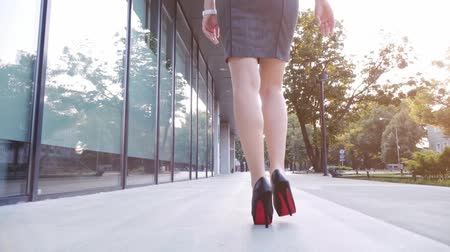 models : Sexy woman legs in black high heels shoes walking in the city urban street. Steadicam stabilized shot, Slow motion. Lens flare. Female legs in high-heeled shoes in the morning. Cinematic shot.