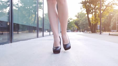 high heel shoe : Sexy woman legs in black high heels shoes walking in the city urban street. Steadicam stabilized shot in Slow motion. Female legs in high-heeled shoes in the morning. Cinematic shot. Stock Footage