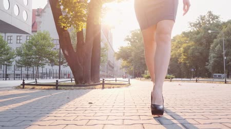 nem városi színhely : Sexy woman legs in black high-heeled shoes. Steadicam stabilized shot, Slow motion. Lens flare. Attractive business woman walking in the city in the morning.