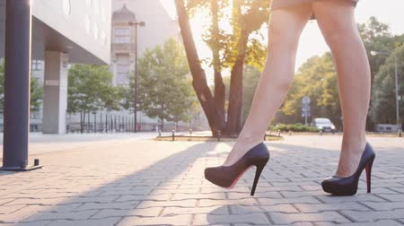 high heel shoe : Sexy woman legs in black high heels shoes walking in the city urban street. Steadicam stabilized shot in Slow motion. Lens flare. Female legs in high-heeled shoes in the morning. Cinematic shot. Stock Footage