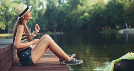 hipster : Attractive young woman listening to music on the music player sitting on a wooden jetty by the lake. Slow Motion, 4K. Happy young girl having fun in the park, enjoying nature and life.