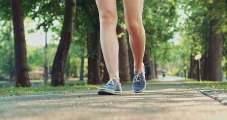 zöld : Female feet in sneakers gumshoes walking and posing on a park road, close up. Womans feet in denim sports shoes passing by the camera. Slow motion, 120fps. 4K, DCi. Stock mozgókép