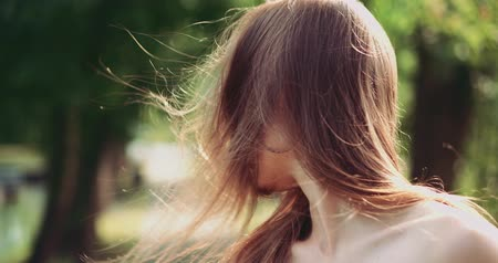 szépség a természetben : Beautiful woman styling hair outdoors. Slow Motion. Happy calm attractive girl with long healthy hair having fun in the park, enjoying nature, playing with the wind. Stock mozgókép