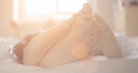 ayak parmakları : Pair of feet playing footsie at home in bed. Slow Motion 120 fps, 4K, DCi. Cozy healthy family morning.  Young couple tenderness. Lens Flare.
