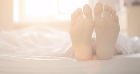 ayak parmakları : Female feet at home in bed, close up. Slow Motion 120 fps, 4K, DCi. Cozy healthy woman morning, comfortable living. Lens Flare.