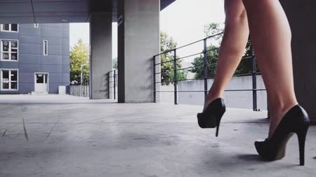 kobieta biznes : Sexy woman legs in black high heels shoes walking in the city urban street. Steadicam stabilized shot, Slow motion. Female legs in high-heeled shoes in the morning. Cinematic shot.