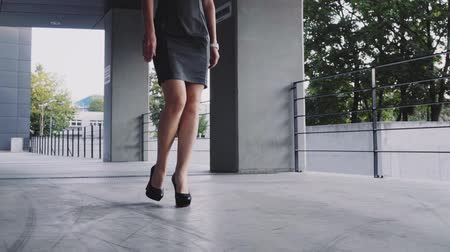 vékony : Sexy woman legs in black high heels shoes walking in the city urban street. Steadicam stabilized shot, Slow motion. Female legs in high-heeled shoes in the morning. Cinematic shot.
