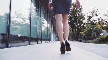 vysoký : Sexy woman legs in black high heels shoes walking in the city urban street. Steadicam stabilized shot, Slow motion. Lens flare. Female legs in high-heeled shoes in the morning. Cinematic shot.