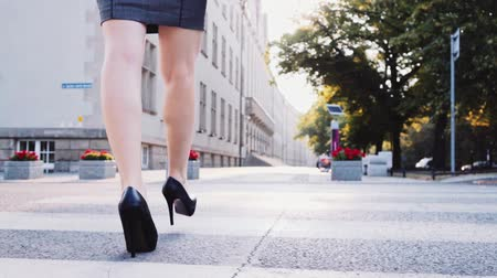 vysoký : Sexy woman legs in black high heels shoes walking in the city urban street, crossing the road. Steadicam stabilized shot in Slow motion. Lens flare. Business woman Cinematic shot.