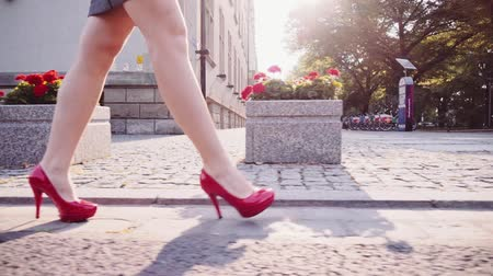 элита : Sexy woman legs in red high heels shoes walking in the city urban street. Steadicam stabilized shot in Slow motion. Lens flare. Female legs in high-heeled shoes in the morning street.