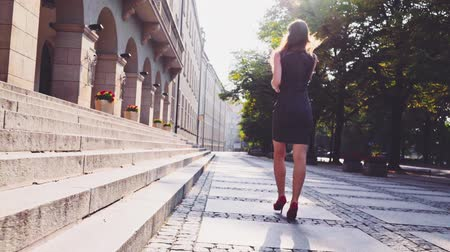 aşağı : Attractive business woman in red high heeled shoes walking in the city, drinking coffee and using a smartphone in the morning. Steadicam stabilized shot in Slow motion. Lens flare.
