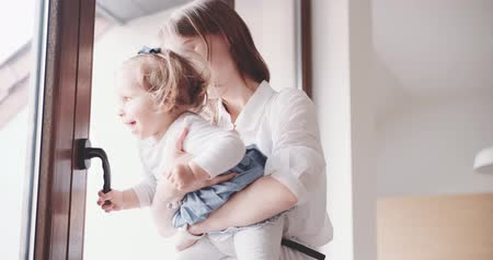unconditional : Mother is playing with child by the window. Slow Motion 120 fps 4K. Young mom holding her baby daughter on her hands. Happy motherhood and childhood concept. Toddler girl 1 year old. Cinematic family Stock Footage