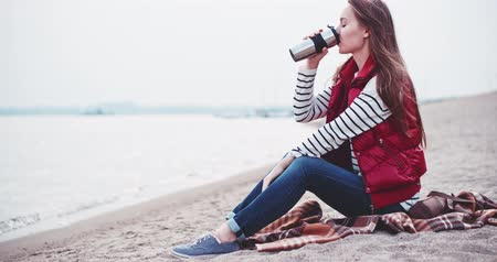 pohárek : Young Woman Relaxing, drinking warm tea or coffee near Lake, Slow Motion 4K DCi. Romantic young woman enjoying cup of a hot drink on the beach. Calm and cozy evening in marina bay. Cinematic shot. Dostupné videozáznamy