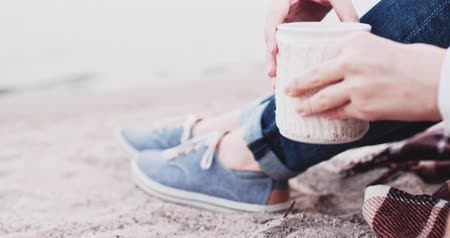 顔写真 : Unrecognizable Woman drinking hot Coffee near Lake, Slow Motion 4K DCi, Close up on cup and shoes. Girl taking her white cup, sitting on the sand. Calm and cozy time in marina bay. Cinematic shot.