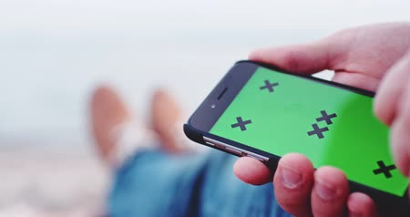 jel : Close Up, Man Using Smartphone Touch Screen, Slow Motion 4K, DCi. Man looking through pages on the phone display, Green Screen Chroma Key For Custom Content. Hipster man with phone on the beach, POV.