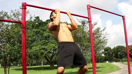 вешать : handsome athletic guy pulls on the bar. Pull ups