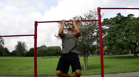 тянущий : Front view. handsome athletic guy pulls on the bar. Pull ups
