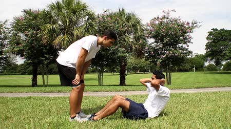 fitnes : Young man doing sit-ups, exercising with personal trainer