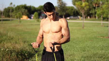 technika : muscular young man doing arm exercises with a resistance band