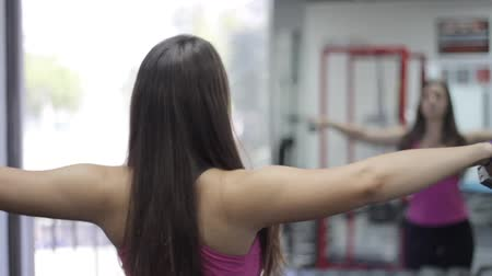 seqüência : beautiful young woman exercising in gym. Shoulders