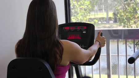 bicycle : Woman exercising on a stationary bike in a gym Stock Footage