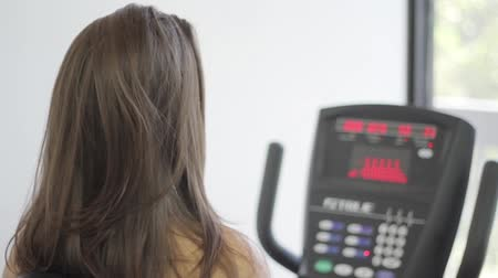 striving : Woman exercising on a stationary bike in a gym Stock Footage