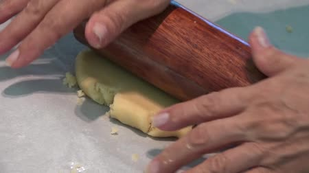 Baker kneading dough with rolling pin on table