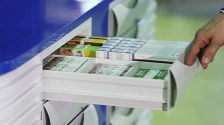 substância : pharmacist taking medicine from shelf at the hospital pharmacy