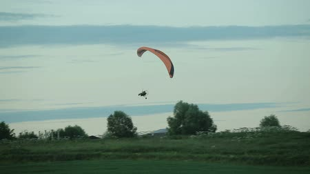 szybowiec : Paraglider flying in the sky over field in the countryside in the evening Wideo
