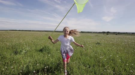 yakalamak : funny girl are playing in field. butterfly net catch butterflies,camera is stabilized on  steadicam