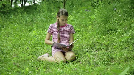 parky : Young girl sitting on green grass reading a book in a meadow in the park Dostupné videozáznamy