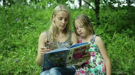 öğretim : Mother with daughter sitting on the green grass reading book outdoors in summer time happy mom teaching her children in the park Stok Video