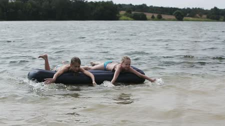 o : Father and daughters on inflatable mattresses swim across the lake.Summer vacation