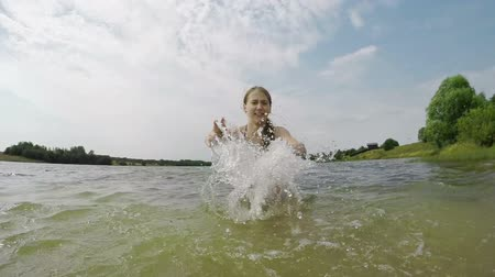 rzeka : Smiling young girl in bikini making splash with water in camera.Family vacations on the lake, river.Summer vacation