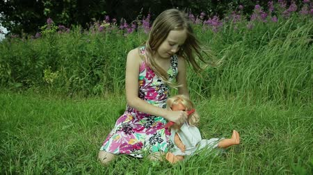 boneca : young girl in beautiful dress sitting on the grass and playing with a doll on a summer day behind the girl flowers combs doll hair