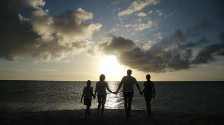 večer : silhouette of family on the beach at sunset