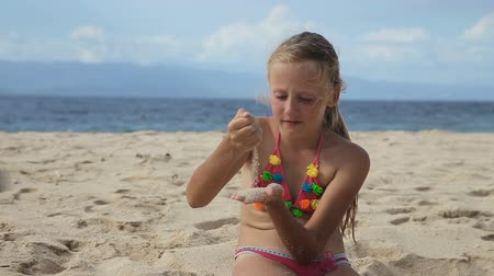 девчушки : Happy child playing with sand on beach in summer.