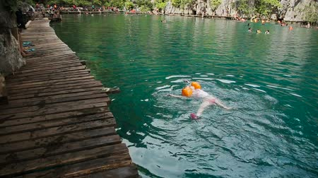 冷却 : Young girl swimming in the beautiful mountain lake, enjoying a swim.Kayangan lake.Travel concept.Family,summer vacation.