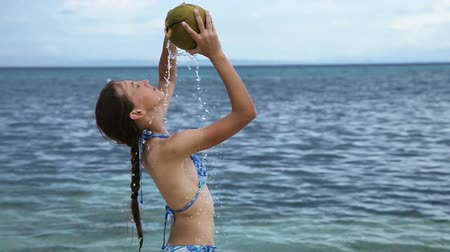 boracay : Young girl on a tropical beach with coconut drink in the hands of coconut juice.Coconut juice flows through the body of a young girl.Travel concept.Family,summer vacation.Happy family.Slow motion Stock Footage