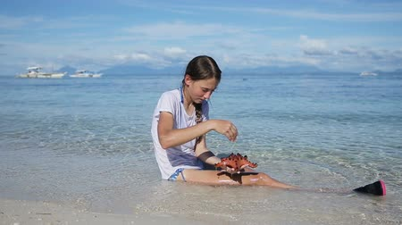 etoile de mer : Girl sitting in the tropical sea, the waves rolled on her feet, she holds a starfish.