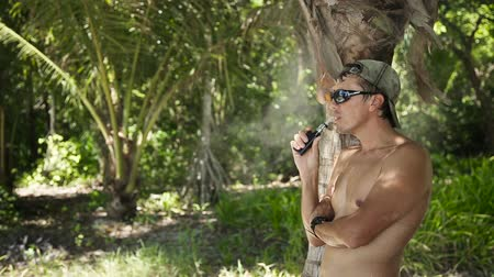 business style : man with an electronic cigarette at the sea.Man in sun glasses stands under the coconut tree and smokes electronic cigarettes