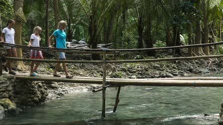 riskli : Family walking on the bridge over the river in the mountainous jungle.Wooden bridge over mountain river in the forest.