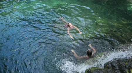 limpid : Young girls swimming in the beautiful mountain lake under waterfall, enjoying a swim.