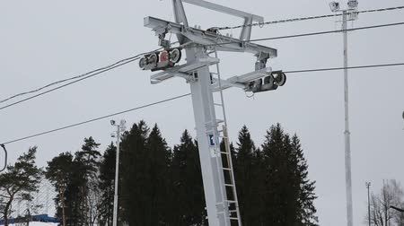 going round : perspective detail ski lift mechanism.Skiers going uphill on ski lift.